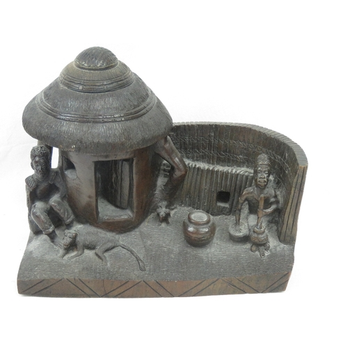409 - Of Ethnographic interest; an unusual heavy carved tribal wood village scene diorama, seated male wit...