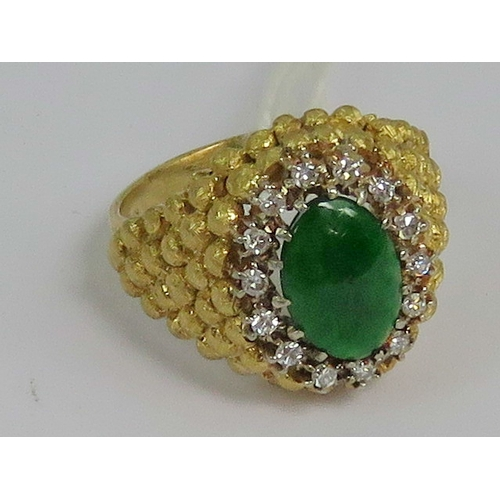 100 - An 18ct gold green jade and diamond ring having unusual beaded yellow metal head with central jade c...