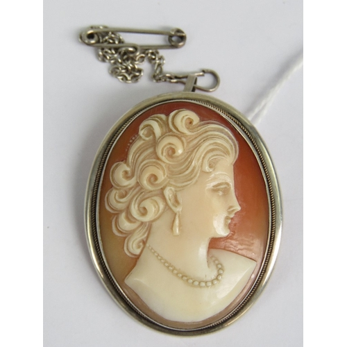 112 - A Continental silver cameo brooch / pendant, the oval carved shell bearing female portrait, the pin ...