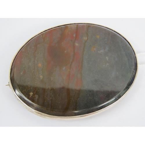 131 - A large HM silver hardstone brooch, the oval cabachon of grey and red hues measuring 5.8 x 4.4cm, se...