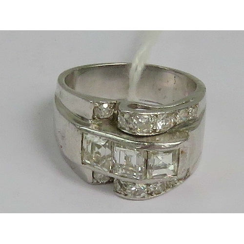 133 - A heavy white metal and diamond ring of abstract form having central row of three square cut diamond...