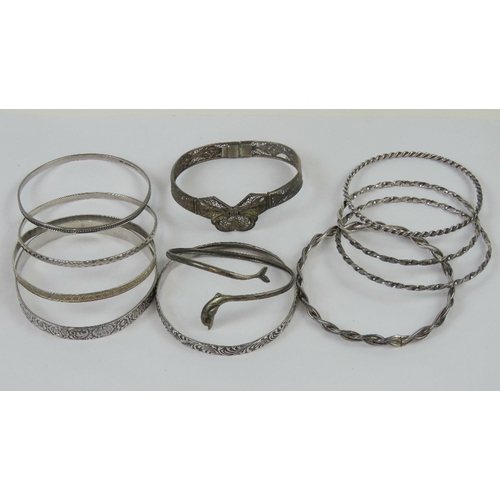109 - Five assorted sterling silver bangles, 1.6ozt, together with an 800 silver dolphin bangle, a white m...