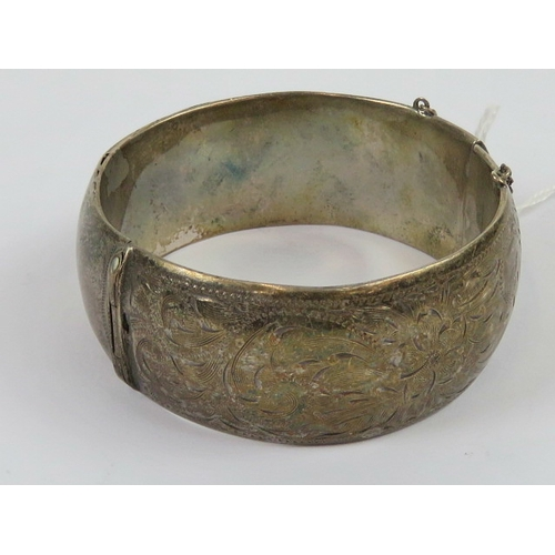100 - A Sterling silver wide cuff bangle having floral engraving to front, approx 6cm internal dia....
