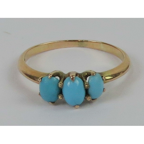 133 - A 10ct gold and turquoise three stone ring, the graduated oval turquoise cabachons in claw settings ...