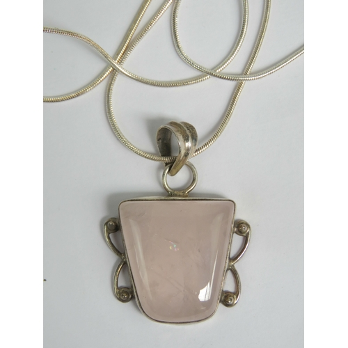 141 - A silver and rose quartz pendant of square form and measuring 4cm in length, complete with silver sn...
