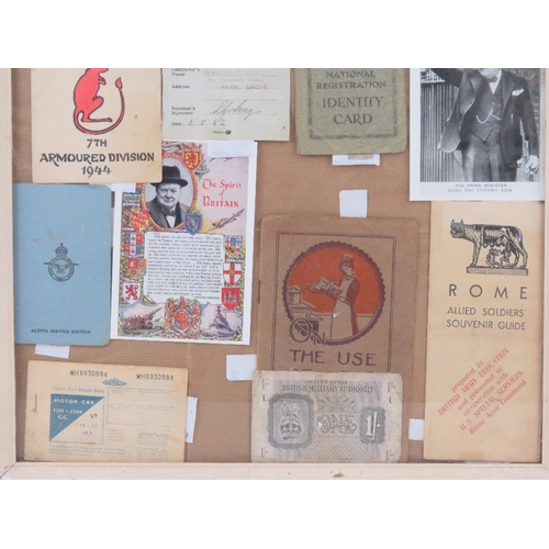 58 - A framed montage of WWII items inc Motorfuel ration book, seventh armored division 1944 Christmas ca...