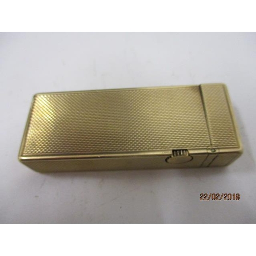 100 - A Dunhill 9ct gold cased cigarette lighter 1962, of rectangular form with engine turned decoration, ...