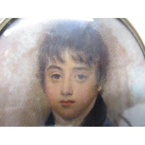 137 - Attributed to William Wood - a portrait miniature of a boy wearing a blue jacket and a long lock of ...