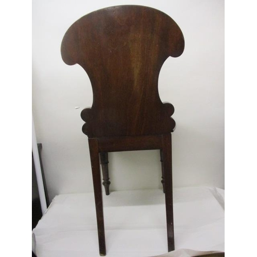 177 - An early Victorian mahogany hall chair having a carved, panelled back and solid seat, raised on turn...
