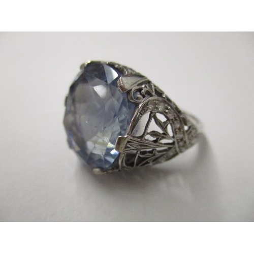 48 - A natural transparent blue sapphire, 21.11ct, set in an ornate white metal ring with diamonds, with ...