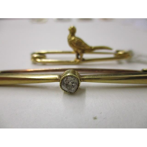 55 - A 15ct gold bar brooch set with a central diamond approximately 0.25ct and a gold coloured bar brooc...
