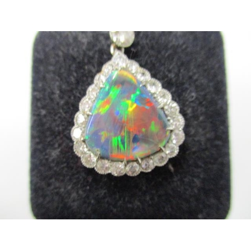 56 - A white metal triangular pendant set with twenty two diamonds around an opal doublet, suspended on t...