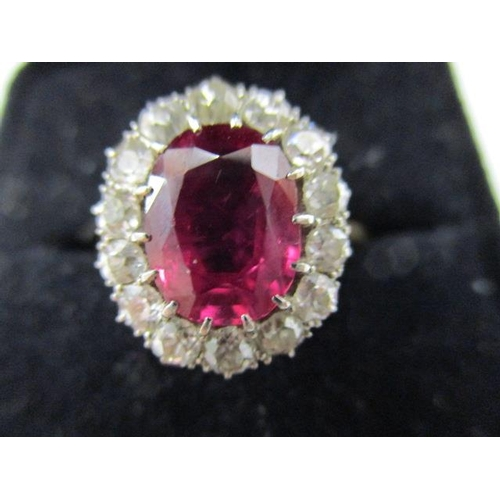 58 - An 18ct gold ring set with fourteen diamonds around a ruby which is approximately 9mm x 7mm...