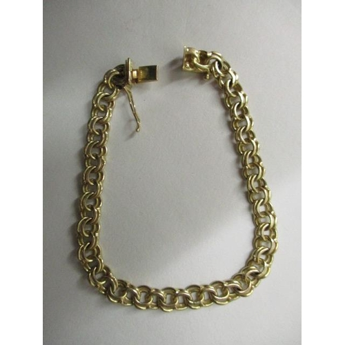 64 - A 9ct gold double ring link bracelet stamped E & AX, 13g...