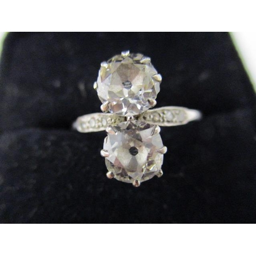 74 - A twin stone diamond ring in a white metal setting with six diamonds to the shoulders, approximately...