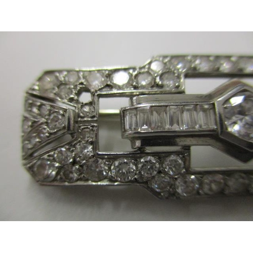 76 - An Art Deco diamond set brooch of openwork, geometric design, set with baguette and brilliant cut di...