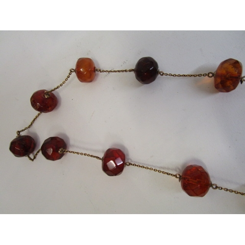 94 - A natural honey amber beaded necklace, some beads with faceted decoration, in a gold plated setting ...