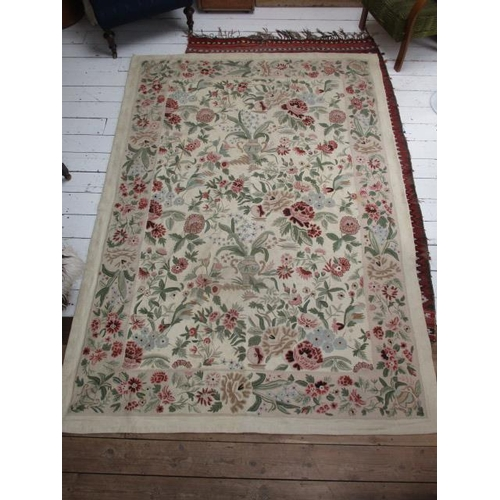 151 - An Aubusson carpet with vases, flowers and foliage in pink, green, brown and black on a cream ground...