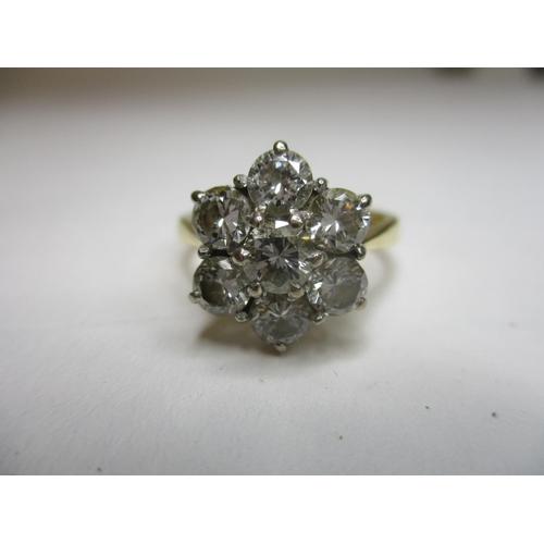 153 - A seven stone diamond cluster ring set in an 18ct gold setting...
