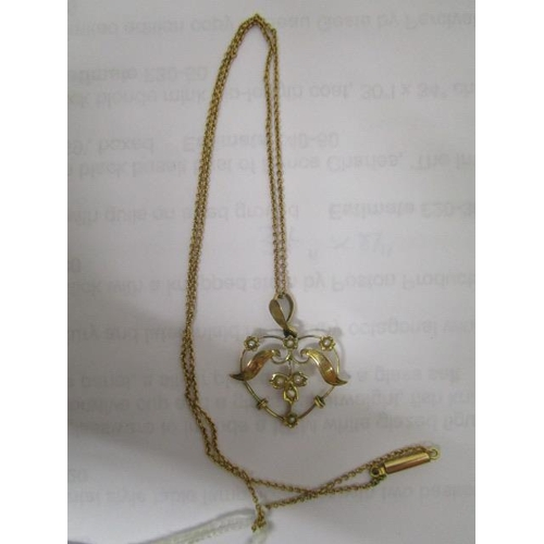 17 - An Edwardian Art Nouveau 9ct yellow gold and split seed pearl pendant on a 9ct gold chain necklace, ...