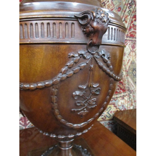 242 - A pair of 1920s mahogany pedestals with canted front corners, a fluted and bead frieze and a door wi...
