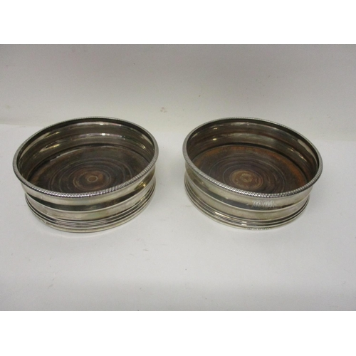 255 - A pair of George III silver wine bottle coasters by IB London 1812 with moulded sides, initialed and...