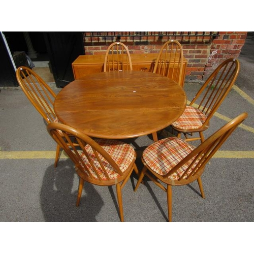 73 - A 1960s Ercol dining room suite comprising a drop flap dining table, six standard dining chairs with...