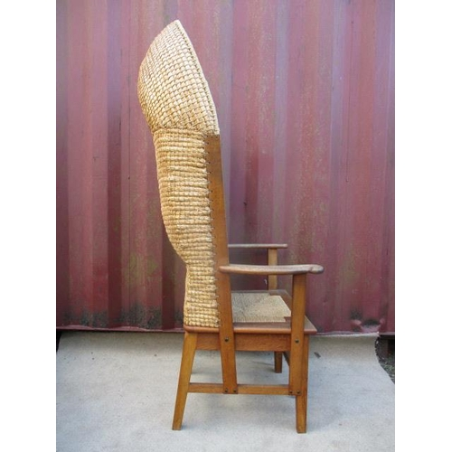 211 - An early 20th century, light oak framed Orkney chair having a rush canopy back, scrolled arms and se...