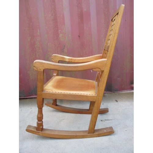 218 - A Robert Thompson Mouseman oak rocking chair with a carved, woven effect back, curved arms and brown...