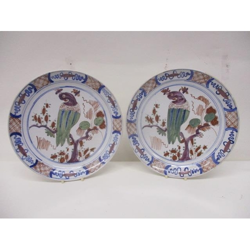219 - A pair o mid 18th century Dutch Delft dishes, decorated in polychrome enamels, with bird perched in ...