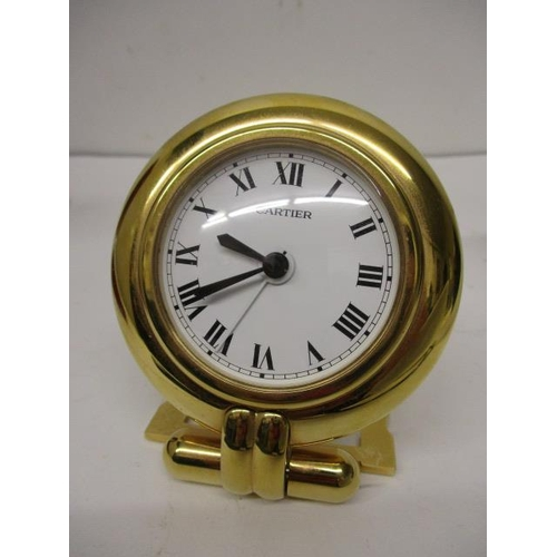 32 - A Cartier quartz gilt metal cased, modern bedside clock having a circular case, white enamel dial an...