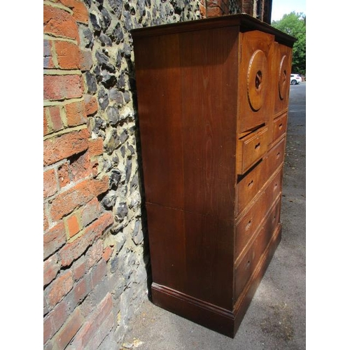 300 - A Heals oak chest having twin panelled doors with rotating, locking handles over two short and three...