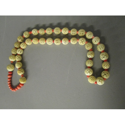 262 - A Chinese Court Mandarin coral and carved ivory, beaded necklace, comprising twelve graduated coral ...