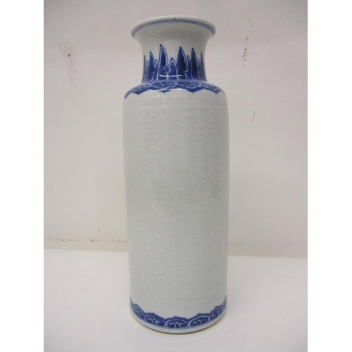 154 - A late 19th century Chinese cylindrical carved, blue and white vase, with a flared neck decorated wi...