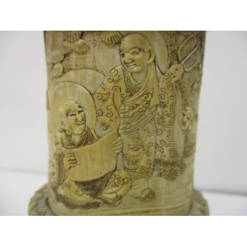 101 - An early 20th century Chinese carved ivory figure sitting cross legged in a niche, under a domed top...