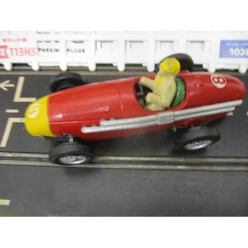 42 - A late 1950s Scalextric boxed set with tin plate cars, track, box to house, the batteries with conne...