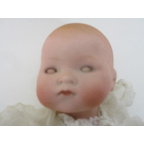 29 - An Armand Marseilles bisque headed doll marked 341. 1 9/10 with cloth body and sleeping eyes, 12