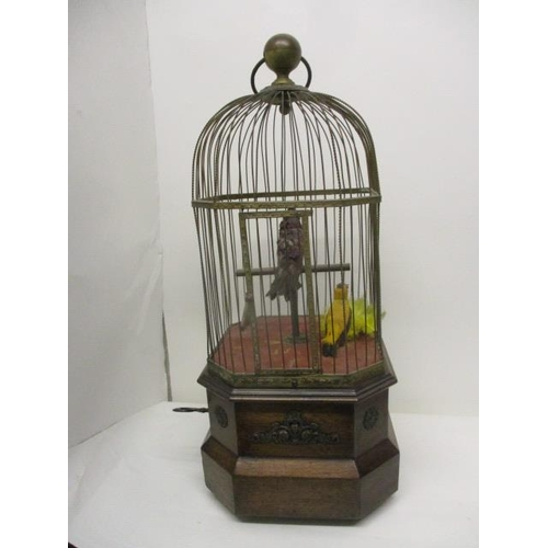 61 - An early 20th century coin operated mahogany and brass, twin bird automaton with a carrying handle, ...