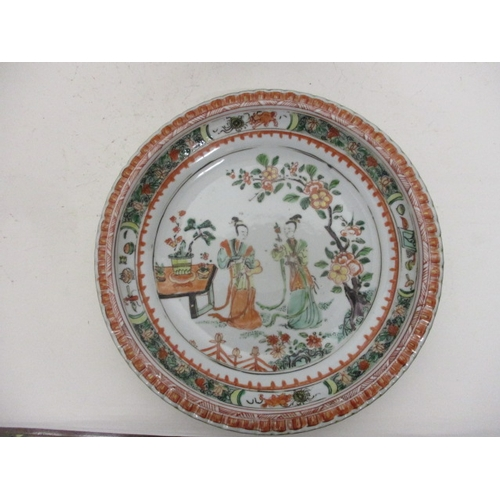 96 - A pair of 18th century Chinese famille vert plates, each decorated with two figures in a garden sett...