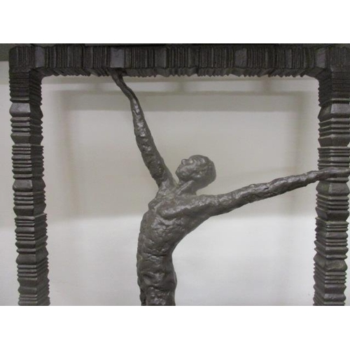 308 - A contemporary cast bronze hall table having a black marble top, over a man with outstretched arms, ...
