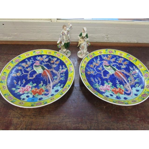 56 - A pair of Sitzendorf porcelain figurines and two oriental porcelain wall plates...