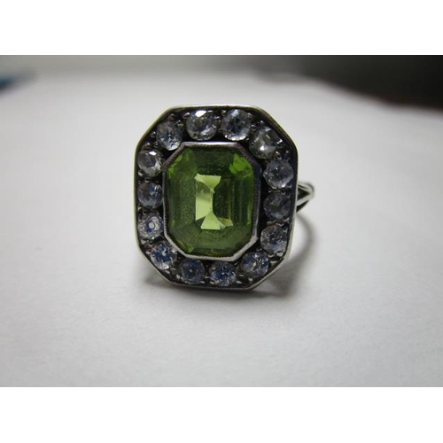 118 - A white coloured metal ring set with a peridot within a border of fourteen diamonds, 15mm x 13mm, ov...