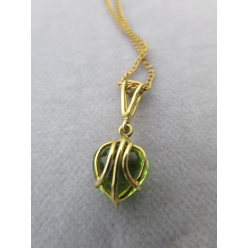 119 - A Mappin & Webb 18ct gold pendant set with a heart shaped peridot, the suspension ring, set with a d...