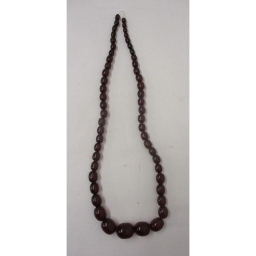 14 - A cherry coloured Bakelite necklace with fifty five beads, 71g...