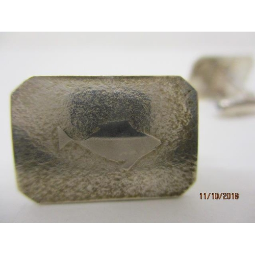 18 - A pair of silver cuff links each of rectangular form with canted corners, each decorated with a fish...