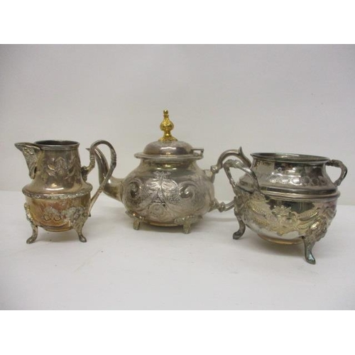 47 - A modern silver coloured metal matched three piece teaset, embossed and chased with flowers and swag...