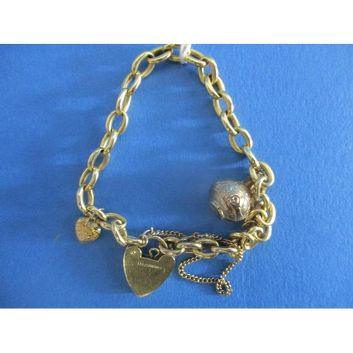 49 - A 9ct gold oval link bracelet with a heart shaped lock and two charms, 24.8g...