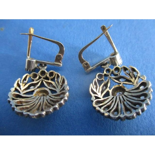 53 - A pair of white and yellow gold coloured metal earrings fashioned as a flower, set with diamond chip...