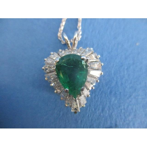 56 - An 18ct white gold heart shaped pendant set with an emerald within a border of tapered baguette diam...