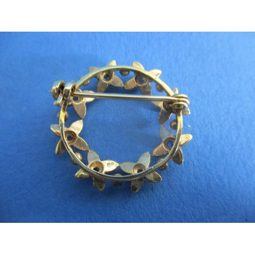 58 - A gold coloured metal brooch fashioned as a ring of eight flowers, each set with a sapphire and four...